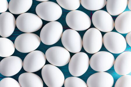 sugarcoated: Background pattern of multiple small white sugar-coated Easter eggs on a blue picnic table viewed as a layer from above