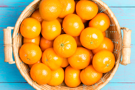 basketful: Fresh ripe juicy clementines in a rustic wicker basket on a blue crackle painted wooden picnic table for a healthy summer snack