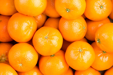 full frame: Food background of fresh healthy ripe orange clementines, tangerines or mandarins in a full frame view rich in vitamin c