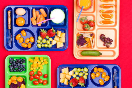veggie tray: Four blue, green and pink plastic lunch trays filled with colorful fruit and vegetables along side milk and juice Stock Photo