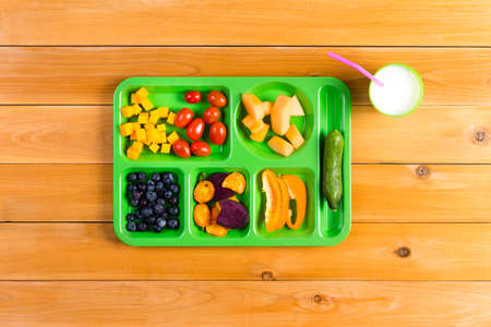 lunch tray: Single green lunch tray filled with dried and fresh fruit next to cup of milk over yellow wooden table background