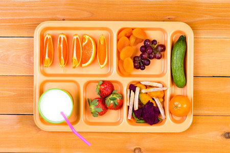 lunchtime: Lunchtime plastic tray filled with orange wedges, dried apricot, grapes, pickle, strawberry and other ingredients next to cup of milk over wooden table background