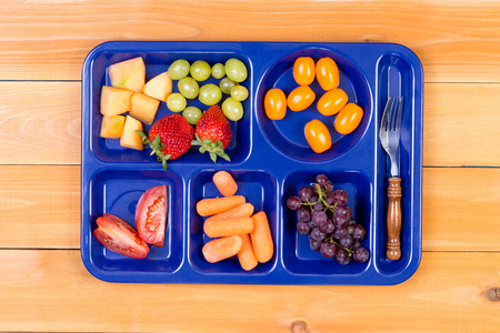 lunch tray: Delicious tangy and sweet fruit sampler of melon, grapes, tomatoes, carrots and grapes in lunch tray with fork Stock Photo