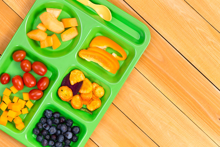 lunch tray: Child size lunch tray with cherry tomatoes, melon, blueberries and sweet pepper fruit on wooden table