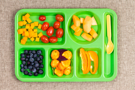 lunch tray: Small rectangular lunch tray with cherry tomatoes, melon, blueberries, sweet pepper and other fruit on surface with cloth texture Stock Photo