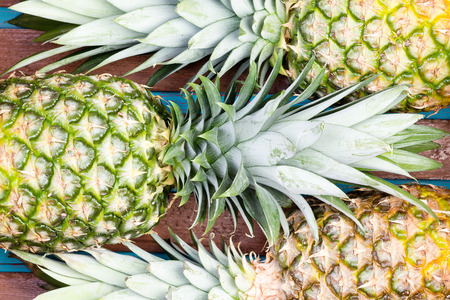 alternating: Three large pineapple fruits placed closely next to each other in alternating arrangement as background Stock Photo