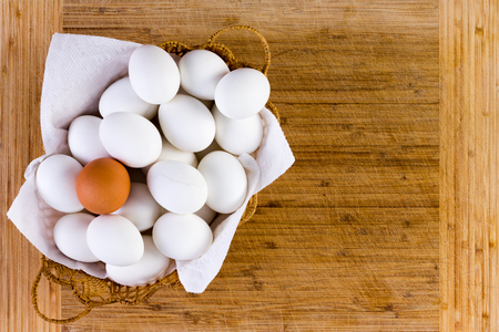 basketful: Basketful of clean white eggs displayed on a napkin with one brown one balanced on top in a conceptual image over a bamboo cutting board with copy space, overhead view Stock Photo