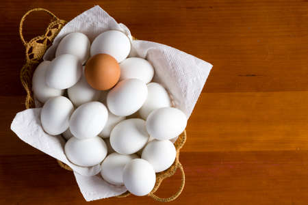 basketful: Wicker basket full of white eggs and single brown type on top over wooden table background with copy space on side