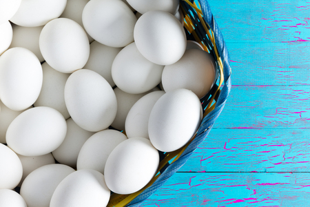 basketful: Wicker basket full of farm fresh clean white hens eggs on a wooden table painted with exotic blue crackle paint with copy space