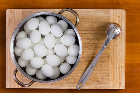 white eggs: Boiled white hens eggs in a metal saucepan or colander standing on a wooden board cooling for decorating with colored dye for the Easter holiday Stock Photo