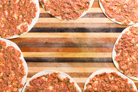 inlaid: Frame of ready to cook traditional Turkish lahmacun on a decorative wooden board with colorful inlaid stripes and central copyspace, overhead view