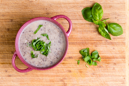 potherb: Delicious homemade cream of mushroom soup with minced fresh mushrooms garnished with chopped basil, overhead view in a ceramic bowl on a bamboo cutting board