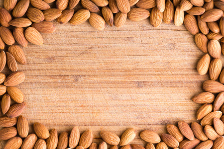 dietary fiber: Rectangular border or frame of fresh raw almonds rich in vitamin e, protein and dietary fiber arranged around an old wooden cutting board with central copy space