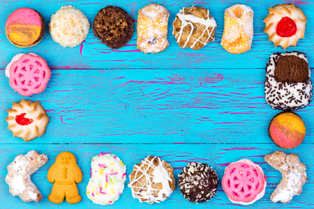 assorted: Rectangular frame of colorful assorted cookies or biscuits on a blue crackle painted wooden background with central copyspace