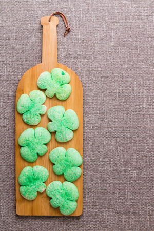 Green shamrock cookies for celebrating St Patricks Day with the Irish served on a bottle shaped board to - Drown the shamrock - with a traditional drink, overhead with copy space Stock Photo