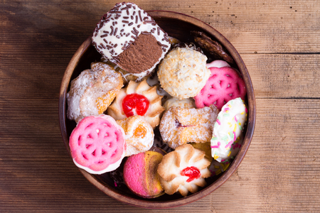 scrumptious: Bowl of colorful delicious assorted cookies with chocolate, glazed biscuits and decorative pink cookies in a rustic bowl on an old wooden table, overhead view