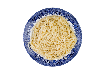 plateful: Plate of plain cooked Italian spaghetti pasta served on a blue plate ready to be served with a savory topping viewed from overhead isolated on white Stock Photo