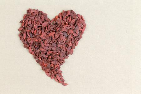 forme et sante: En forme de coeur formé de baies de goji séchées sains ou wolfberries sur une texture fond crème avec copie espace conceptuel de la bonne santé et de l'alimentation