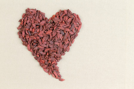 cream colored: Heart shape formed of healthy dried goji berries or wolfberries on a textured cream colored background with copy space conceptual of good health and diet Stock Photo