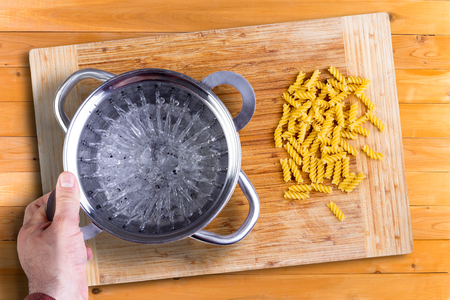 stainless steel pot: Man preparing to cook dried Italian rotini pasta laid out on a wooden cutting board holding a stainless steel pot in his hand, overhead view on a wooden kitchen counter Stock Photo