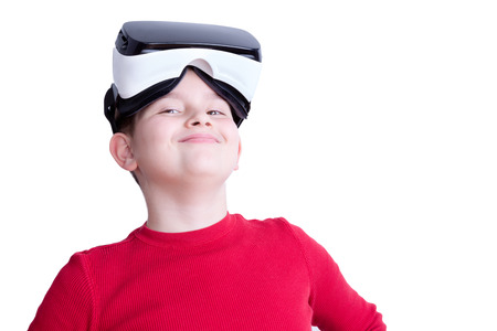 One boy with virtual reality glasses on his head wearing a red shirt stands proudly against a white background