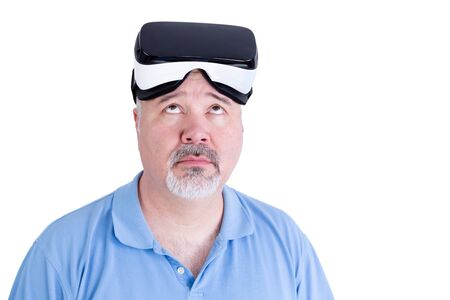 realtime: Adult male with virtual reality glasses on his head wearing blue polo shirt against a white background looks up questioning Stock Photo