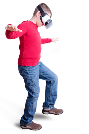 Boy wearing red long sleeved shirt and blue jeans with virtual reality glasses takes a step with arms outstretched