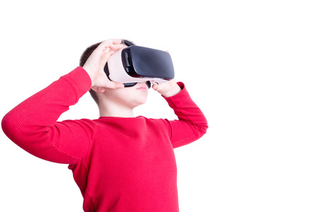 long sleeve shirt: Serious male child in red long sleeve shirt holding and looking through virtual reality glasses over white background
