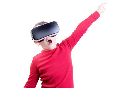 mesmerized: Excited single young male child wearing red shirt with arm up while flying or pointing with virtual reality headset