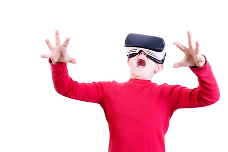Amazed young child wearing red shirt experiencing a shocking explosion while wearing a virtual reality headset