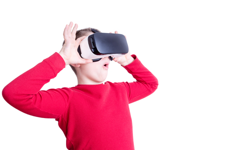 Fascinated male child in red long sleeve shirt holding and looking through virtual reality glasses over white background