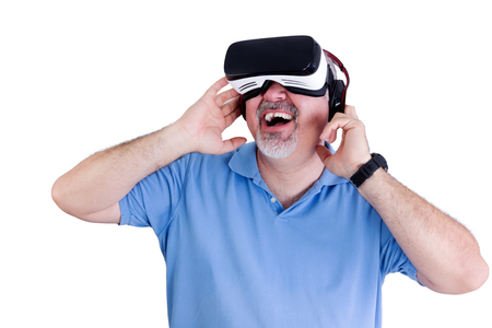 tecnology: Laughing man in blue polo shirt holds both hands to either side of the virtual reality glasses positioned on his face