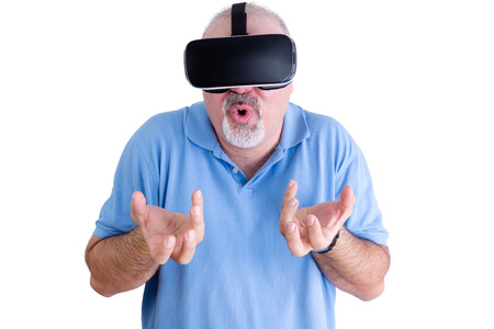 reacts: Man in blue polo shirt reacts to wearing virtual reality glasses by grabbing at the air with both hands and rounding his lips Stock Photo