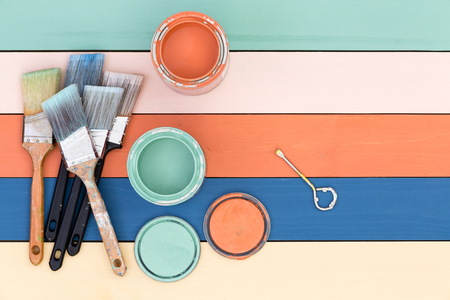 Colorful multicolored stained wood background in pastel shades with painting supplies of opened tins of stain and clean paintbrushes with copy space, overhead view