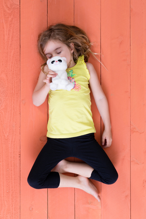 legs folded: Cute supple young girl sleeping with her plush toy cat held to her face lying on her back with folded legs on a colorful orange wooden deck, viewed from overhead Stock Photo