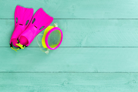 Vibrant colorful kids goggles and flippers arranged neatly in the corner on a pastel green stained wooden deck conceptual of a summer seaside holiday, overhead with copy space Stock Photo