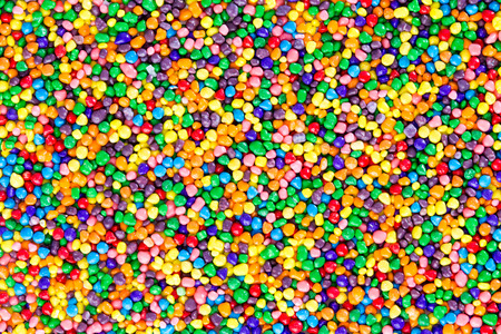 full frame: Background texture of colorful sugar candy pearls in the colors of the rainbow viewed overhead in a layer full frame