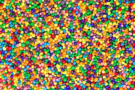 paleta de pintor: Textura del fondo de perlas de colores del caramelo de azúcar en los colores del arco iris fue vista por encima en un cuadro completo de capa Foto de archivo