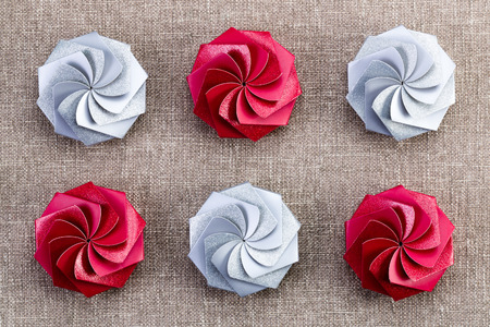 alternating: Six colorful red and silver Christmas gift boxes with a decorative swirled spiral pattern viewed from above in alternating rows Stock Photo