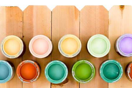 stain: Opened pots of colorful wood stain arranged as a lower border on a natural wooden picket fence offering a choice of colors to suit your decor Stock Photo