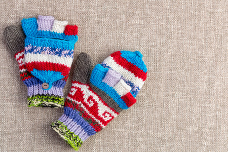 fold back: Colorful hand knitted convertible fingerless winter gloves with a fold back cap to cover the tips of the fingers as required on a beige textile background with copy space