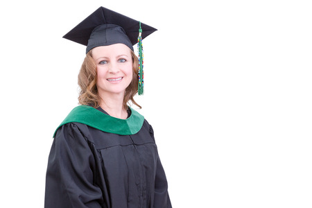 tertiary: Pretty middle-aged academic in graduation clothing wearing a mortarboard cap and gown looking at the camera with a pleased happy smile, upper body on white with copy space