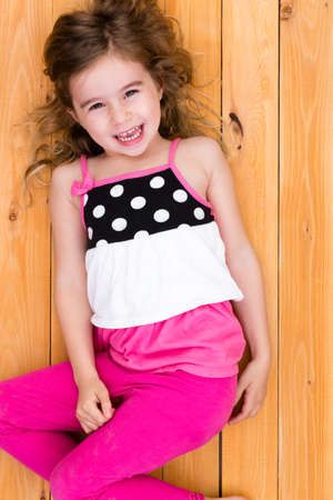 girl looking up: Cute happy little girl lying on the floor in a stylish pink outfit with polka dots looking up at the camera and laughing Stock Photo