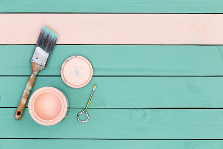 paintcan: Top down view of paintbrush, bolt, paintcan and green boards for paneling or flooring starting to be painted pink Stock Photo