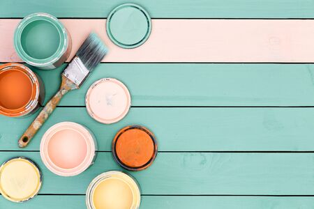 Renovation theme background of floor boards or wooden fence under yellow, pink, orange and green paint cans and brush with copy space