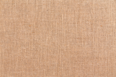 Full frame brown woven burlap or hessian textile background texture made from woven natural fibres viewed close up overhead