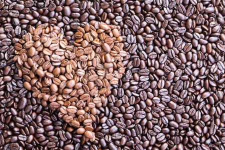 inset: Background made from overhead view of heart shaped pile of coffee beans inset among darker ones spread across a surface Stock Photo
