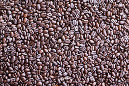 addictive drinking: Background made from overhead view of coffee beans spread across a surface