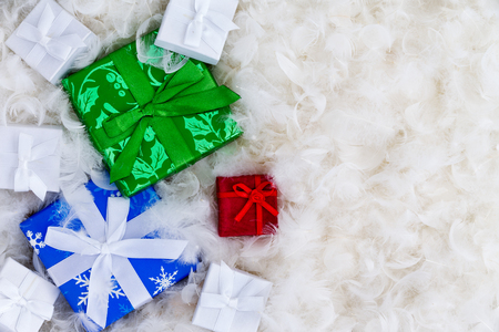giftwrapped: Various little wrapped boxes in blue, green, red and white with copy space surrounded by feathers for expensive gift concept