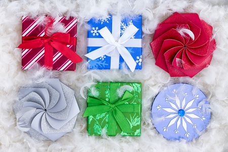 padding: Top down view on six Christmas gift boxes surrounded by fluffy padding that resembles snow or white feathers for luxury concept Stock Photo